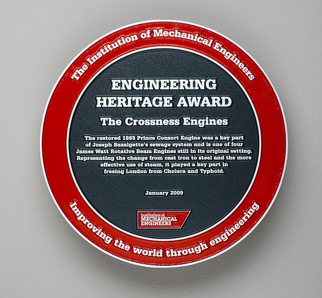 Joseph Bazalgette red and black plaque - The Crossness Engines The restored 1865 Prince Consort Engine was a key part of Joseph Bazalgette's sewage system and is one of four James Watt Rotative Beam Engines still in its original setting. Representing the change from cast iron to steel and the more effective use of steam, it played a key part in freeing London from Cholera and Typhoid.