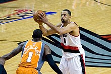 Black athlete holds a basketball while a defender with his back to the camera plays defense