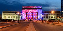 A large neoclassical building lit up red and blue with white stars.