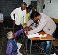 A handicapped old registering his name to cast his vote at a polling booth of Khujji Assembly constituency, during the first phase of polling for Assembly Election in Chhattisgarh on November 11, 2013.jpg
