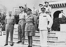 Eight men stand on the steps of a Middle Eastern building. Six wear various uniforms but one wears a business suit.