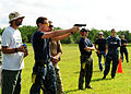 Andrew Degitz, left, and U.S. Navy Gunner's Mate 1st Class Ken Shumate, third from left, assigned to Naval Surface Warfare Center Indian Head, supervise a Sailor firing an M9 pistol during a weapons 130822-N-FJ200-034.jpg