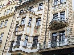 Vue rapprochée d'une façade art nouveau, des bow-windows saillants et des balcons triangulaires sont visibles.