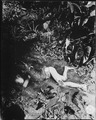 Atrocity committed by the Japanese on 9 April 1945 at Bingas, Luzon, Philippine Islands. Child laying in mud of creek. - NARA - 531318.tif