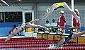 Australian swimmer diving off starting blocks.jpg