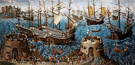 A small fleet of large, highly decorated carracks are riding on a wavy sea. In the foreground are two low, fortified towers bristling with cannons and armed soldiers and an armed retinue walking between them.