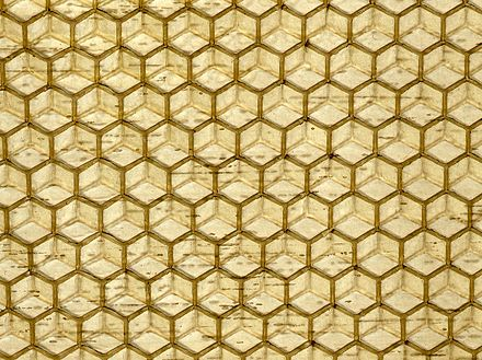 Commercial honeycomb foundation, made by pressing beeswax between patterned metal rollers. Beeswax foundation.jpg