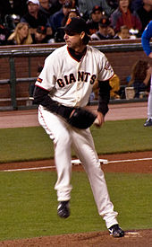 "A man in a white baseball uniform with the word ""GIANTS"" written across it prepares to throw a baseball with his left hand to home plate during a game."