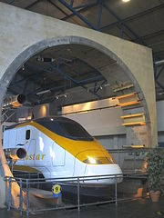 The Channel Tunnel exhibit at the National Railway Museum in York, England. The exhibit shows the circular cross section of the tunnel with the catenary (overhead) wires powering a Eurostar train. Also visible is the segmented tunnel lining.