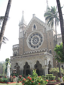 The front of a tall neo-Gothic building with a porch is seen behind palm trees.