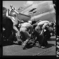 Crewmen hastily drag plane with flat tire down flight deck of USS Lexington (CV-16) to make way for next plane to land. - NARA - 520903.jpg