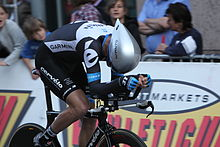 A road racing cyclist, wearing a black and white skinsuit with blue trim and an aerodynamic helmet, sits crouched very low on his bicycle. Spectators watch from the roadside.