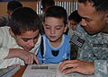 Defense.gov News Photo 101003-N-7062A-002 - U.S. Navy Petty Officer 1st Class Rodolfo Duqu right practices conversational English with children of Afghan National Army soldiers at Camp.jpg