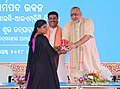 Dharmendra Pradhan and the Minister of State for Micro, Small & Medium Enterprises (IC), Shri Giriraj Singh felicitating a divyang daughter Ms. Gauri Gauda, at the National SC-ST Hub State Conclave and Exhibition.JPG