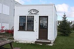 """Malá dřevěná chatka, bíle natřená, se znakem """"Advokátní kancelář JG Diefenbaker 1919–1925"""