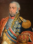 Painting of an overweight man with gray hair, bulging round eyes and a double-chin. He is clothed in a dark blue uniform that is covered by decorations and gaudy decorations. His left hand rests on a crown.