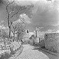 Dorpsgezicht met een moskee, een minaret en enkele huizen en muren langs een weg, Bestanddeelnr 255-1191.jpg