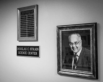 Electro Scientific Industries - Framed photograph of Douglas C. Strain, on the wall of the science center named after him at Pacific University