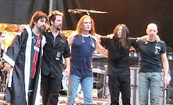 Five male musicians standing on stage. They are standing in an arc, and their hands are on each other's shoulders.