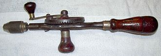 "Drill - An old hand or ""eggbeater"" drill with hollow wooden handle and screw-on cap, used to store drill bits"