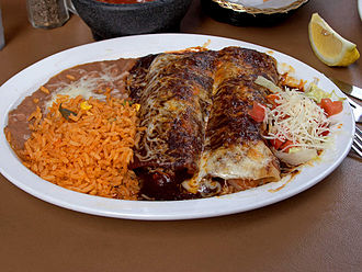 Enchilada - Enchiladas with mole, served with refried beans and Spanish rice