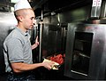 Fireman Apprentice Dillon Wike, an electrician's mate puts bacon in an oven in the galley aboard amphibious dock landing ship USS Pearl Harbor (LSD 52) 101020-N-KB563-117.jpg