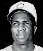"A head shot of an African-American man with a white baseball cap with a red ""C"" in the center."