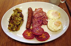 Full English breakfast with bubble and squeak, sausage, bacon, grilled tomatoes, and eggs.jpg