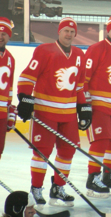 A hockey player in full uniform wearing a toque. He is in a red uniform in white trim with a stylized