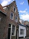 foto van Huis met trapgevel van gele baksteen met banden en vensterafzetting van rode baksteen