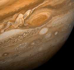 This dramatic view of Jupiter's Great Red Spot and its surroundings was obtained by Voyager 1 on February 25, 1979, when the spacecraft was 9.2 million km (5.7 million mi) from Jupiter. Cloud details as small as 160 km (100 mi) across can be seen here. The colorful, wavy cloud pattern to the left of the Red Spot is a region of extraordinarily complex and variable wave motion. To give a sense of Jupiter's scale, the white oval storm directly below the Great Red Spot is approximately the same diameter as Earth.