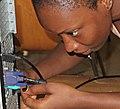 Guinean woman installing computer.jpg