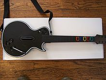 A black guitar controller sits on a white piece of paper and a wooden floor.