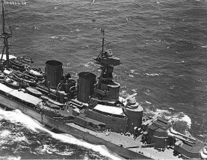 HMS Hood - Aerial view of Hood in 1924. The two forward gun turrets are visible with their prominent rangefinders projecting from the rear of the turret. Behind the turret is the conning tower surmounted by the main fire-control director with its own rangefinder. The secondary director is mounted on top of the spotting top on the tripod foremast.