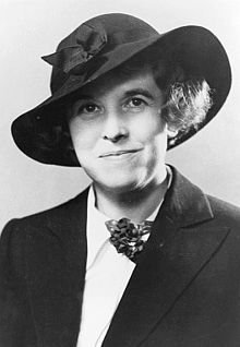 A woman in a black tilted hat and black suit sits at bust length and looks directly into the camera