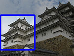 A three-storied castle tower with white walls and a dark roof on a platform of unhewn stones. It is connected to a two-storied structure.