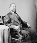 A black and white photograph of an African American male in a suit sitting with a table on his right side