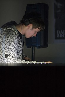 A man in his twenties with short messy brown hair concentrates on the decks in front of him with headphones tucked above his ear whilst wearing a white and black patterned hoody.