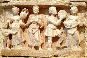Lute - Hellenistic banquet scene from 1st century A.D., Hadda, Gandhara. Lute player with short-necked lute, far right.