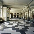 Interieur, overzicht van de hoofdentree met een arcade op zuilen, tegelvloer en klassieke beelden - 's-Gravenhage - 20387427 - RCE.jpg