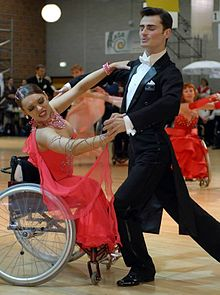 A wheelchair-bound woman in a ball gown dances with a man in a tuxedo