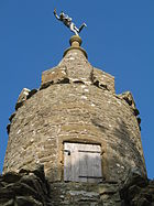 Circular tower with wooden door. On the top is a small statue.