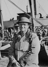 A middle-aged man posing for a photo wearing a World War II-era military uniform. The superstructure of a ship and the bow of a boat are visible behind him
