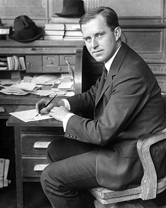 Young man in his twenties in a suit, seated and looking back toward the camera