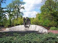 Uma parede baixa de pedra, curvando-se para cima.  Três estátuas de soldados poloneses estão montadas em seu centro.  Abaixo das estátuas, o texto é montado conforme a legenda.