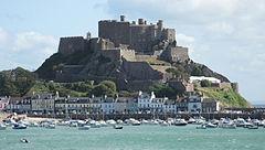 Zdjęcie przedstawia położony na wzgórzu zamek Mont Orgueil w miejscowości Gorey. Na zdjęciu widać wielki, kamienny zamek z kilkoma wieżyczkami i różnymi poziomami murów, znajdujący się na wzgórzu, którego jedno zbocze opada bezpośrednio do morza. Twierdza góruje nad niewielkim miasteczkiem w którym widać kilka kamieniczek i mały port, pełny małych łódek.