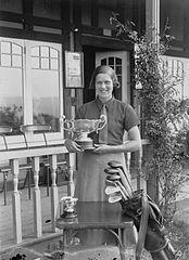 Lady holding a trophy outside Llandrindod Wells Golf Club pavilion