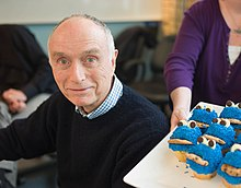 White male in his 70s, wearing a dark blue sweater, to the left of a woman holding a tray of Cookie Monster cupcakes