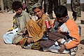 Local boys chat and eat a snack, outside of the Zhari District Center in Kandahar province, Afghanistan, Dec. 24, 2011 111224-A-VB845-161.jpg