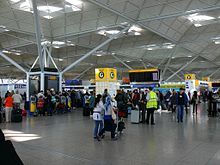 "Stansted Airport departures hall. There is a crowd of people waiting for their flight. In the middle of the image, there is a large yellow pole with directions on it. In the middle of the pole is a large letter ""G"""